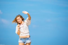 Young skinny caucasian girl waving with blue sky Royalty Free Stock Photography