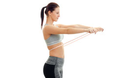 Young skinny girl stands sideways and keeps at the waist measuring tape Stock Photo