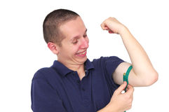 Young skinny man measuring his muscle. Happy young skinny man measuring his muscle Stock Photos