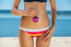 Young, skinny, pretty girl in a striped bathing suit holding a pink Christmas ball in hand, on the ocean, the sea. Royalty Free Stock Photography