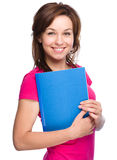 Young skinny student girl is holding exercise book Royalty Free Stock Photo