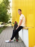 Young skinny boy teenager sitting near yellow wall with long board. A beautiful sunny day for skateboarding. stock image