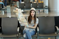 Young slaphappy traveler tourist woman holding paper map, search route, wait in lobby hall at international airport. Passenger traveling abroad on weekends royalty free stock photo