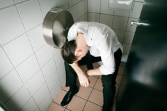 Young sleeping drunk man on the toilette Stock Image