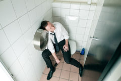 Young sleeping drunk man on the toilette Royalty Free Stock Image