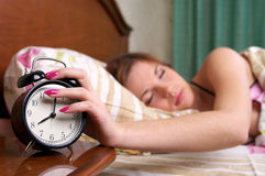 Young sleeping female turns alarm Stock Image