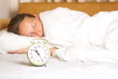 Young sleeping woman and alarm clock in bed Royalty Free Stock Images