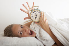 Young sleeping woman and alarm clock in bed Royalty Free Stock Photos