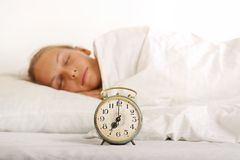 Young sleeping woman and alarm clock in bed Royalty Free Stock Image