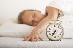 Young sleeping woman and alarm clock in bed Royalty Free Stock Photo