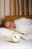 Young sleeping woman and alarm clock in bed Stock Images