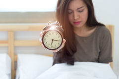 Young sleeping woman and alarm clock Royalty Free Stock Photos