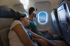 Young sleeping woman lying on the male shoulder while traveling. Young sleeping women lying on the male shoulder, both wearing headphones, while traveling by Royalty Free Stock Photography