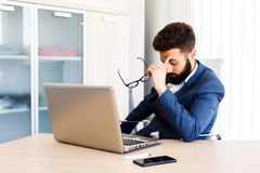 Young Businessman Has Stressful Day At Work. Young Sleepy Business Man Sitting At Workplace - In office Royalty Free Stock Photo