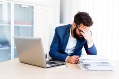 Young Handsome Businessman Has Headache. Young Sleepy Business Man Sitting At Workplace - In office Stock Image