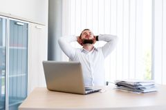 Young Handsome Businessman Has Headache. Young Sleepy Business Man Sitting At Workplace - In office Stock Photo