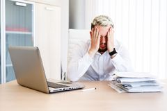 Young Handsome Businessman Has Headache. Young Sleepy Business Man Sitting At Workplace - In office Royalty Free Stock Photos
