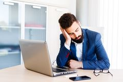 Young Sleepy Businessman Sitting At Workplace. Young Sleepy Business Man Sitting At Workplace - In office Stock Image