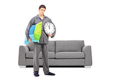 Young sleepy guy holding a wall clock and pillow, with modern so Stock Photography