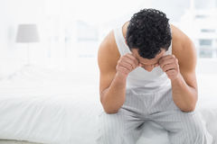 Young sleepy man rubbing his eyes on bed Stock Photos