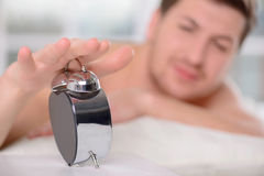 Young sleepy man turns off the alarm clock Stock Photo