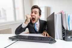 Young sleepy and tired man is yawning at work in office Royalty Free Stock Image