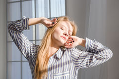 Young sleepy woman stretching with closed eyes Stock Images