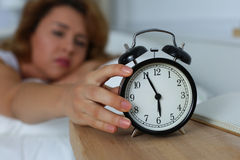 Young sleepy woman trying to turn off the alarm clock Royalty Free Stock Image