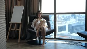 A young slender beauty sits in a chair by the window. stock video