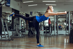 Young slender blond woman doing exercises in gym stock image