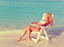 The young slender blonde in bikini a beach chair at ocean in a sunny day Royalty Free Stock Photography