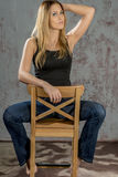 Young slender blonde girl in jeans and shirt posing coquettishly Royalty Free Stock Photos