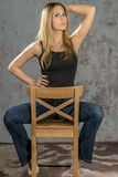 Young slender blonde girl in jeans and shirt posing coquettishly Royalty Free Stock Images