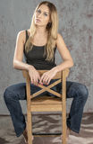 Young slender blonde girl in jeans and shirt posing coquettishly Royalty Free Stock Photography