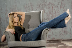 Young slender blonde girl in jeans and shirt posing coquettishly Stock Photography