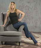 Young slender blonde girl in jeans and shirt posing coquettishly Stock Photo