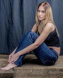 Young slender blonde girl in jeans and shirt posing coquettishly Stock Image