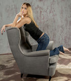 Young slender blonde girl in jeans and shirt posing coquettishly Royalty Free Stock Photo