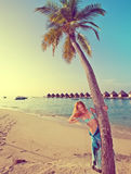 The young slender blonde stands near palm tree, Maldives,with a retro effect Royalty Free Stock Photos