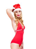 Young slender blonde to red sexual a bathing suit and a red cap of Santa Claus on a white background Royalty Free Stock Image