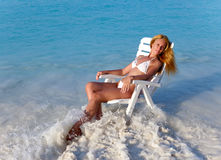 The young slender blonde in white sexual bikini a beach chair at ocean Royalty Free Stock Images