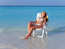 The young slender blonde in white sexual bikini a beach chair at ocean in a sunny day Stock Images