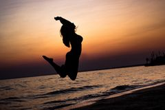 Young, slender girl gracefully jumping on the sand in the sea at sunset. the concept of freedom of life. place under the text. Woman jumping on sand at the sea Royalty Free Stock Photos