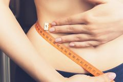 Young slender girl measures the waist, close-up. Sixty centimeters stock photo