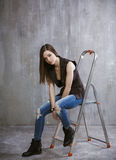 Young, slender girl sits on a stepladder on a background of gray Royalty Free Stock Photos
