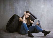 Young, slender girl is sitting near the tires and looking at the Royalty Free Stock Photography