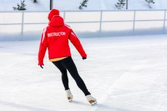 A young slender girl skates and helps beginners royalty free stock image