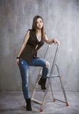 Young, slender girl standing on a a stepladder on a background o Royalty Free Stock Photography