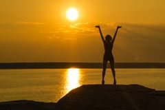 A young slender girl stands on top of a mountain holding her hands up towards the sun in the sunset. royalty free stock images