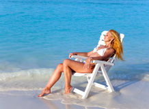 The young slender girl  in white sexual bikini a beach chair at ocean in a sunny day Stock Photography